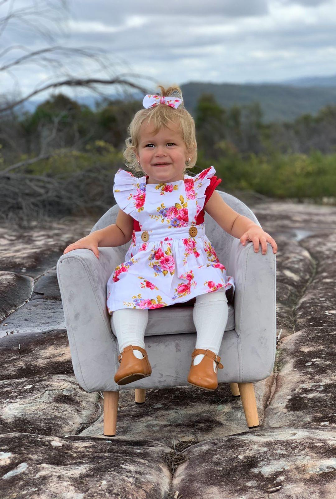 baby girl sitting on sofa-chair while on floral pinny dress
