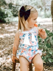 Gorgeous baby girl licking candy and posing while on skylar bow playsuit dress