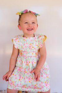Cute laughing girl posing while on flutter pinny dress