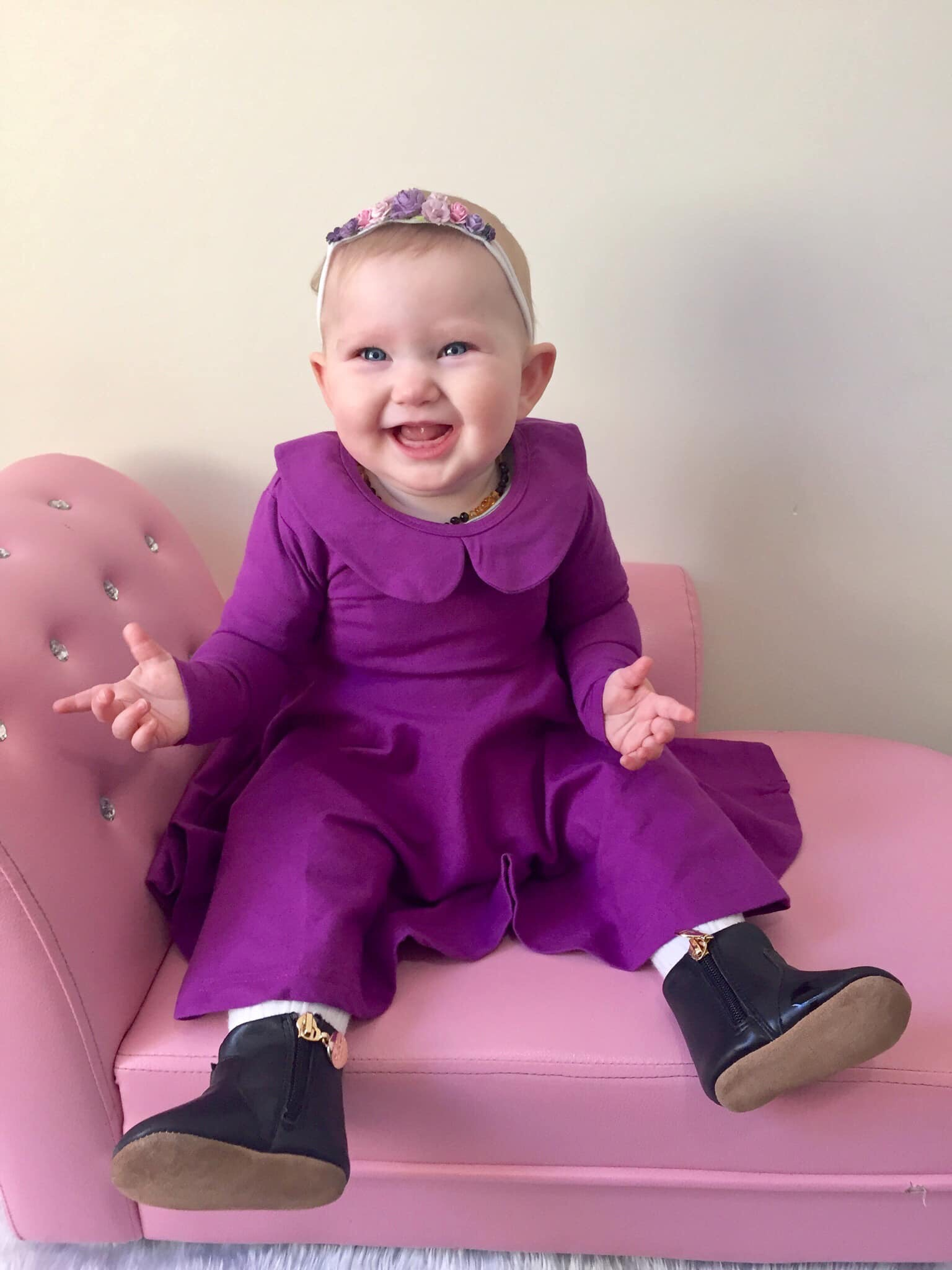 Baby smiling while on violet twirly dress
