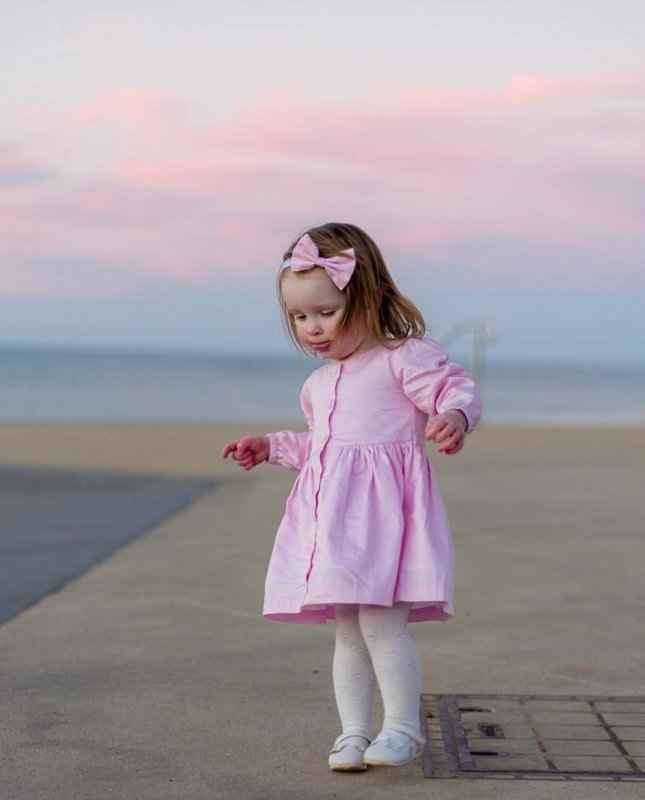 Baby girl wearing pink button dress