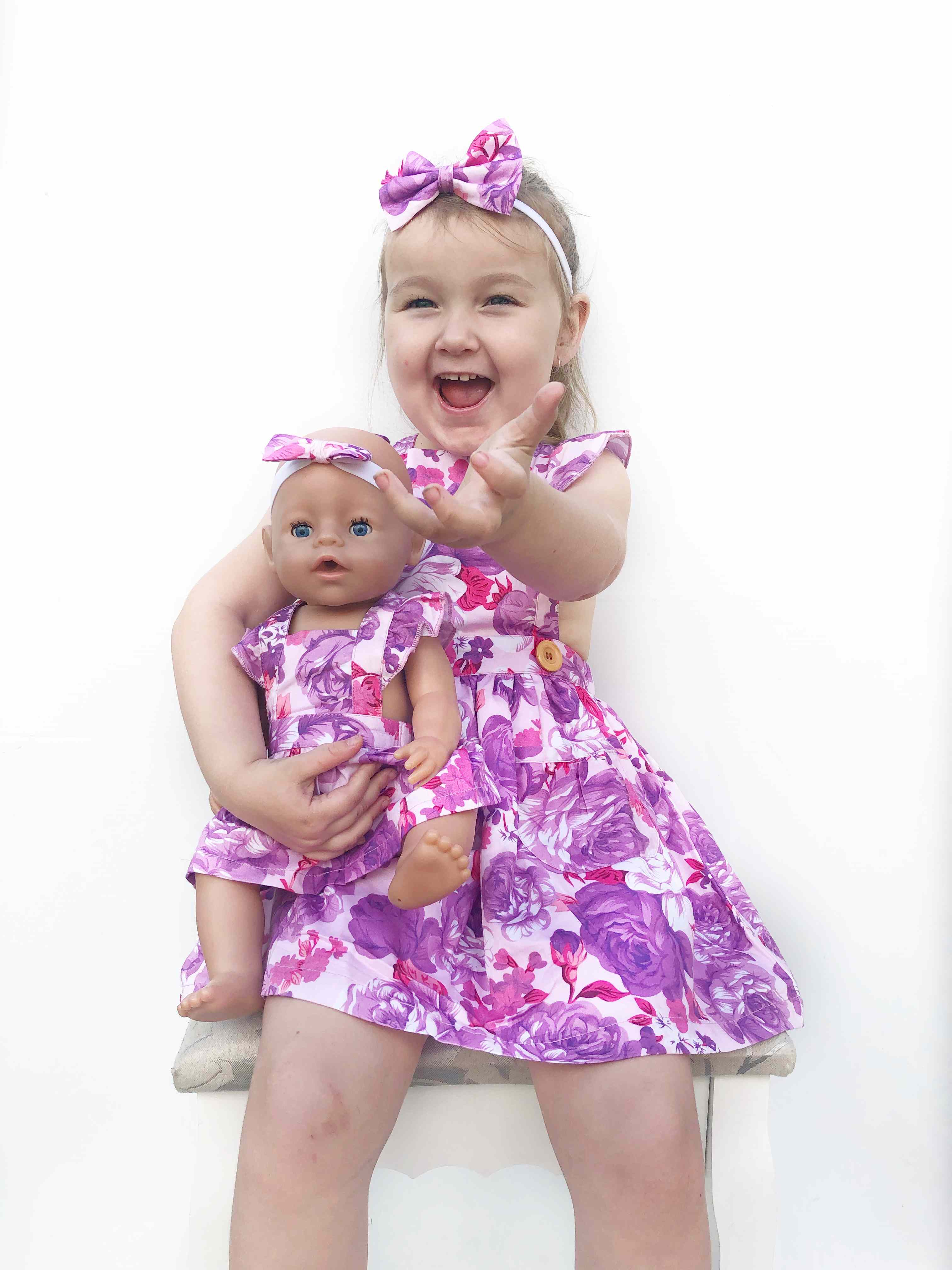laughing girl holding her doll while on ciara flutter dress