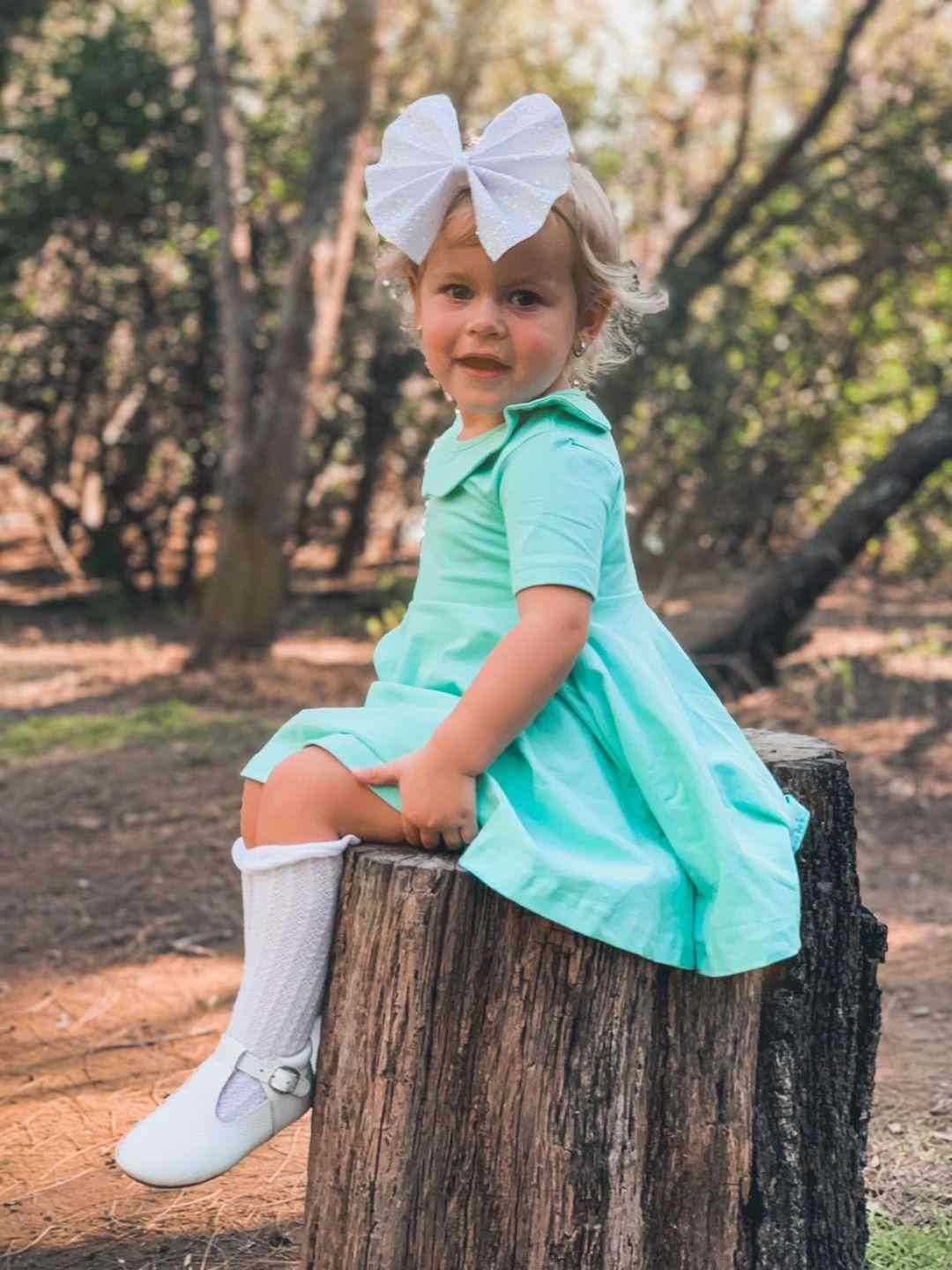Baby girl sitting on wood while on mint color cutest twirly dress