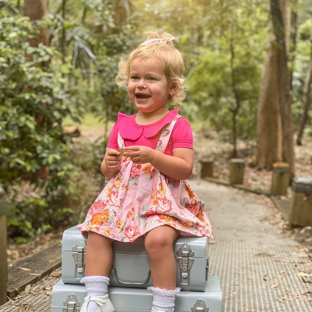 Cute baby girl laughing while on bonnie suspender skirt
