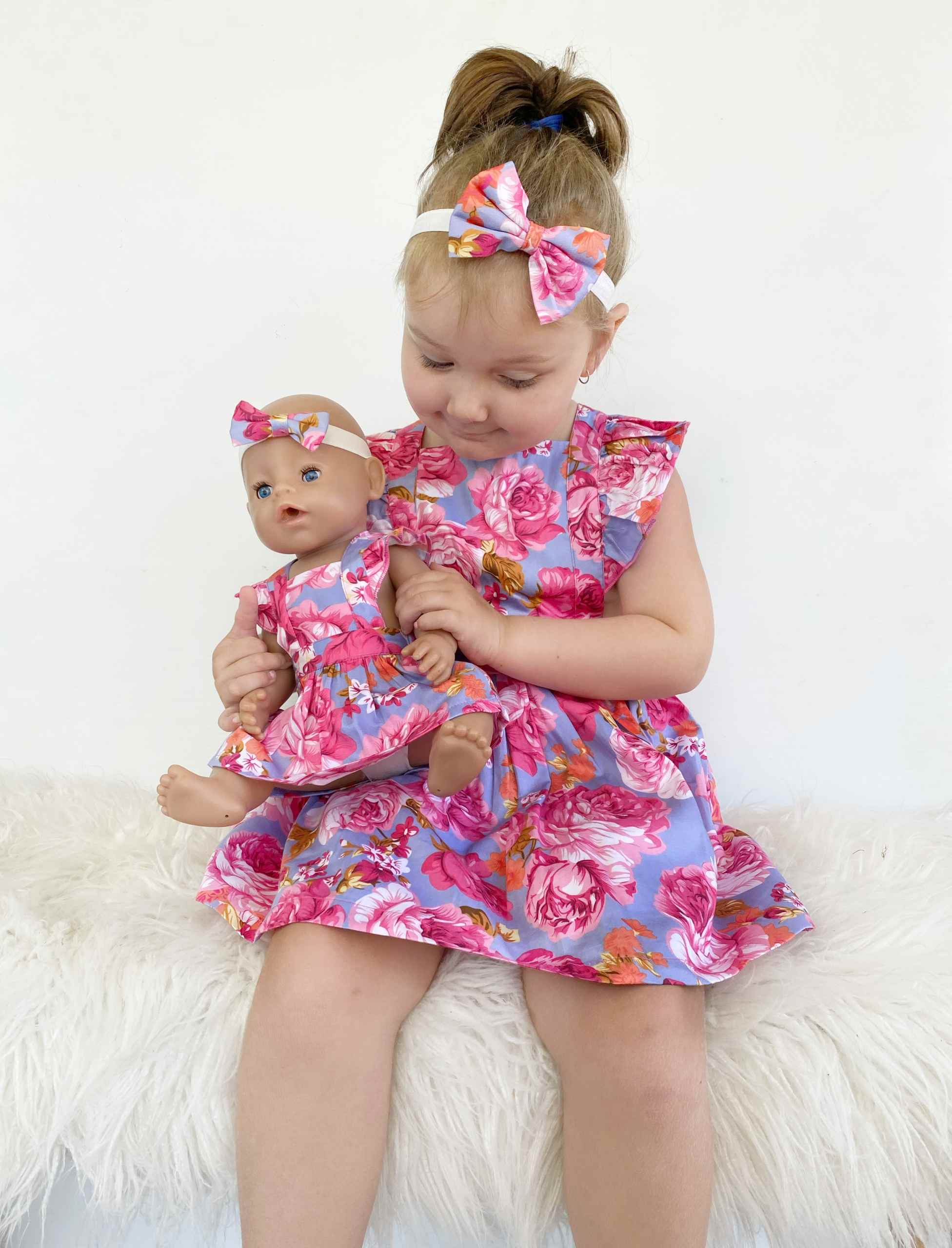 A girl and her dolly matching in floral pinafore