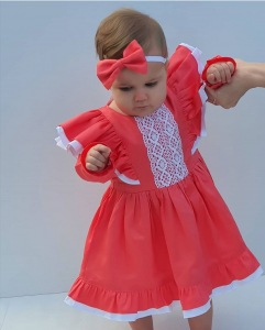 Baby wearing coral ruffles dress